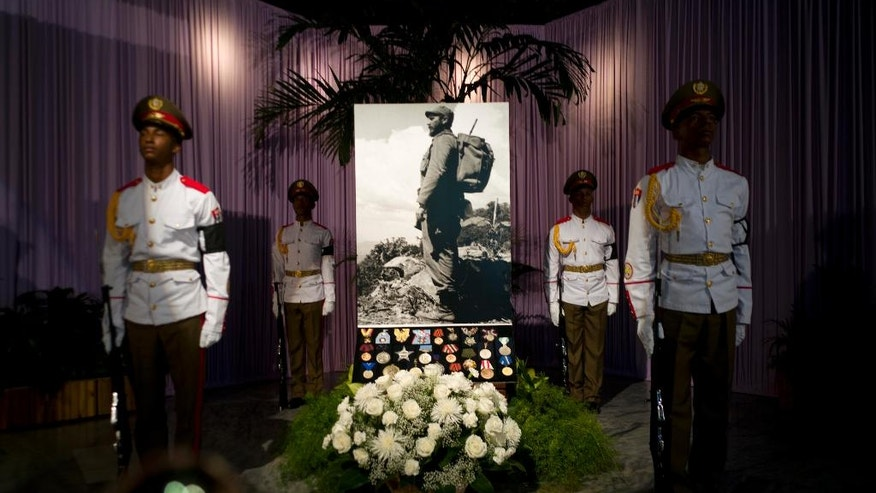 An honor guard flanks an image of Fidel Castro during a tribute to the late leader at the monument to independence hero Jose Marti, at Revolution Square in Havana, Cuba, Monday, Nov. 28, 2016. The square will be the site of two days of tributes to Castro. Cuba's government has declared nine days of national mourning following Castro's death Friday night at age 90. (AP Photo/Ramon Espinosa)