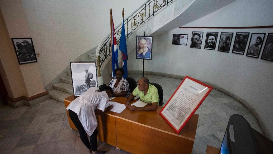 A woman signs a book of condolences, and a loyalty oath for the late Fidel Castro at the Journalists and Writers Union Federation building in Havana, Cuba, Monday, Nov. 28, 2016. Cubans on Monday began bidding farewell to Castro, the man who ruled the island for nearly half a century. (AP Photo/Desmond Boylan)