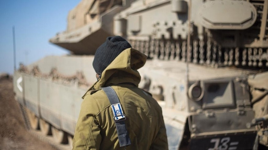 An Israeli soldier stand by a tank near the border with Syria in the Israeli-controlled Golan Heights, Monday, Nov. 28, 2016. The Israeli military says it has carried out an air strike in Syria on a building used by Islamic State militants to attack Israeli forces. The overnight air strike Monday targeted an abandoned United Nations building that Israel says was used as a base by the militants. (AP Photo/Ariel Schalit)