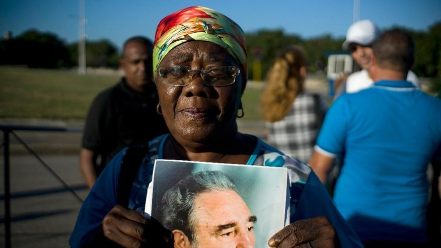 A woman holds an image of Fidel Castro as she waits in line to pay her final respects to the late leader, in Havana, Cuba, Monday, Nov. 28, 2016. Thousands of Cubans began lining up early for the start of week-long services bidding farewell to the man who ruled the country for nearly half a century. Cuba's government has declared nine days of national mourning following Castro's death Friday night at age 90. (AP Photo/Ramon Espinosa)