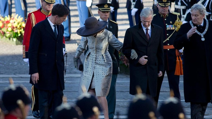 Dutch Prime Minister Mark Rutte, left, turns around as the heel of the shoe of Queen Mathilde of Belgium gets stuck in between the cobblestones as she walks with King Philippe towards the National Monument on the start of their three-day visit to The Netherlands, in Amsterdam, Monday, Nov. 28, 2016. (AP Photo/Peter Dejong)