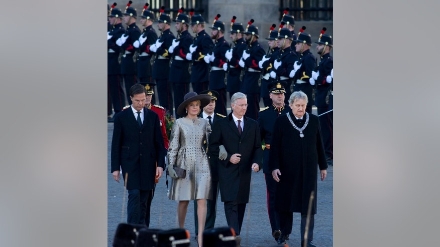 King Philippe and Queen Mathilde of Belgium, center, Dutch Prime Minister Mark Rutte, left, and Amsterdam mayor Eberhard van der Laan, right, walk towards the national monument on Dam square on the start of the three-day visit of the Belgian royal couple to The Netherlands, in Amsterdam, Monday, Nov. 28, 2016. (AP Photo/Peter Dejong)