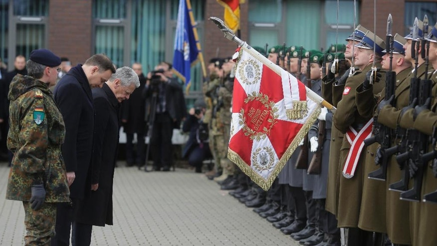 Polish President Andrzej Duda, second from left, and German President Joachim Gauck, third from left, bow to the honor guards during a visit to  the Headquarters of the Multinational Corps Northeast of the NATO, in Szczecin, Poland, Monday, Nov. 28, 2016. (AP Photo/Markus Schreiber)