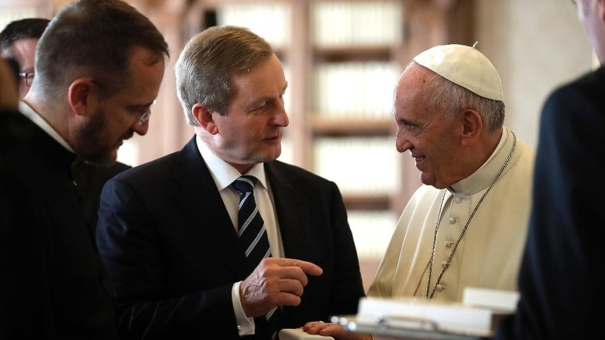 Pope Francis  exchanges gifts with Irish Prime Minister Enda Kenny during a private audience in his private studio at the Vatican, Monday, Nov. 28, 2016. (AP Photo/Alessandra Tarantino, pool )