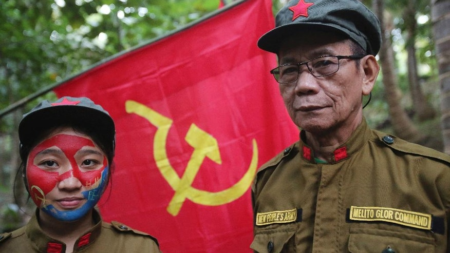In this Nov. 23, 2016 photo, New People's Army's new regional rebel commander and spokesman Jaime Padilla, right, who uses the nom de guerre Comrade Diego, poses beside Comrade Katryn who had her face painted to conceal her identity at their rebel encampment tucked in the harsh wilderness of the Sierra Madre mountains southeast of Manila, Philippines. Young Filipino rebels represent a new generation of Maoist fighters, who reflect the resiliency and constraints of an insurgency that has dragged on for nearly half a century through six Philippine presidencies. Crushing poverty, despair, government misrule and the abysmal inequality that has long plagued Philippine society were their best recruiter, according to the guerrillas. (AP Photo/Aaron Favila)