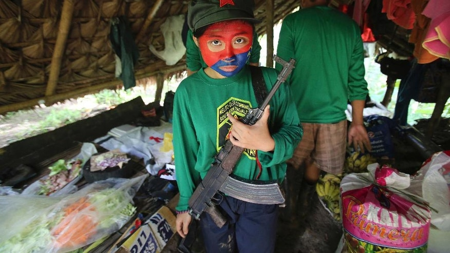 In this Nov. 23, 2016 photo, a woman New People's Army guerrilla with face painted to conceal her identity holds her firearm inside a makeshift shelter at their rebel encampment tucked in the harsh wilderness of the Sierra Madre mountains, southeast of Manila, Philippines. Young Filipino rebels represent a new generation of Maoist fighters, who reflect the resiliency and constraints of an insurgency that has dragged on for nearly half a century through six Philippine presidencies. Crushing poverty, despair, government misrule and the abysmal inequality that has long plagued Philippine society were their best recruiter, according to the guerrillas. (AP Photo/Aaron Favila)