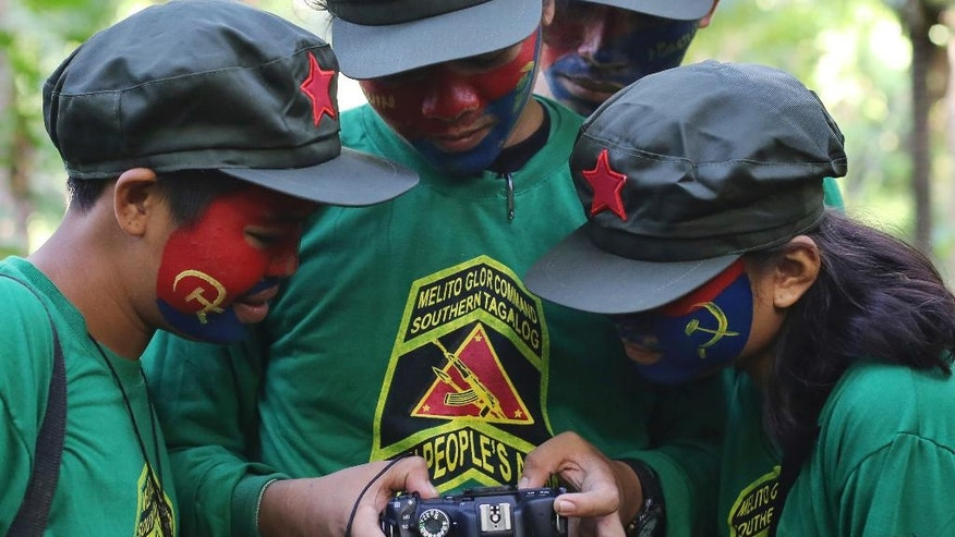In this Nov. 23, 2016 photo, New People's Army guerrillas with face painted to conceal their identities look at photos from their digital camera at their rebel encampment tucked in the harsh wilderness of the Sierra Madre mountains southeast of Manila, Philippines. Young Filipino rebels represent a new generation of Maoist fighters, who reflect the resiliency and constraints of an insurgency that has dragged on for nearly half a century through six Philippine presidencies. Crushing poverty, despair, government misrule and the abysmal inequality that has long plagued Philippine society were their best recruiter, according to the guerrillas. (AP Photo/Aaron Favila)