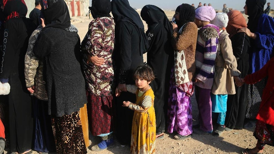 Iraqi citizens who fled the fighting between the Islamic State militants and the Iraqi forces, line up to receive aid supplies and clothes, in the Samah front line neighborhood, in Mosul, Iraq, Nov. 28, 2016. The offensive to free Mosul of Islamic State militants is now in its second month, and progress has slowed as troops try to avoid mass civilian casualties. (AP Photo/Hussein Malla)