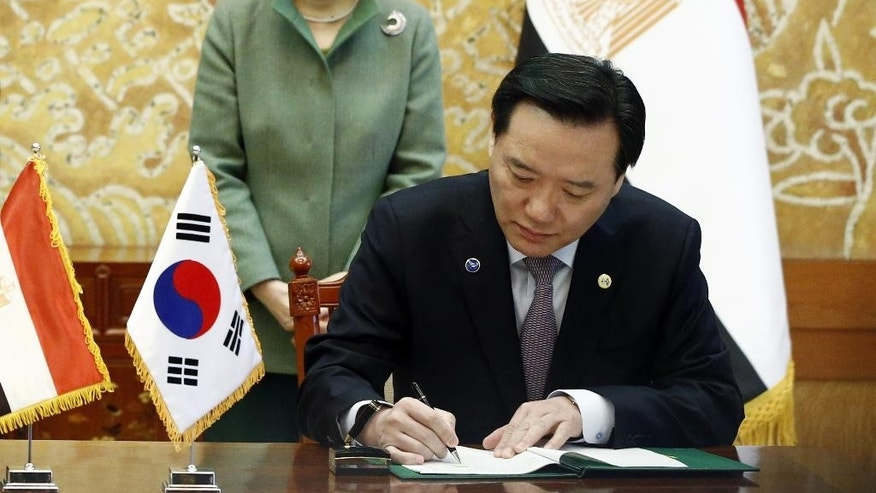 FILE - In this March 3, 2016 file, South Korean President Pak Geun-hye, left, looks at Justice Minister Kim Hyun-woong signing the agreement with Egypt's Foreign Minister Sameh Shoukry at the presidential house in Seoul. South Korea's embattled president has accepted the resignation of her justice minister, the latest in a series of personnel reshuffles she's made amid a political scandal that's threatening her leadership. (Jeon Heon-kyun/Pool Photo via AP, File)