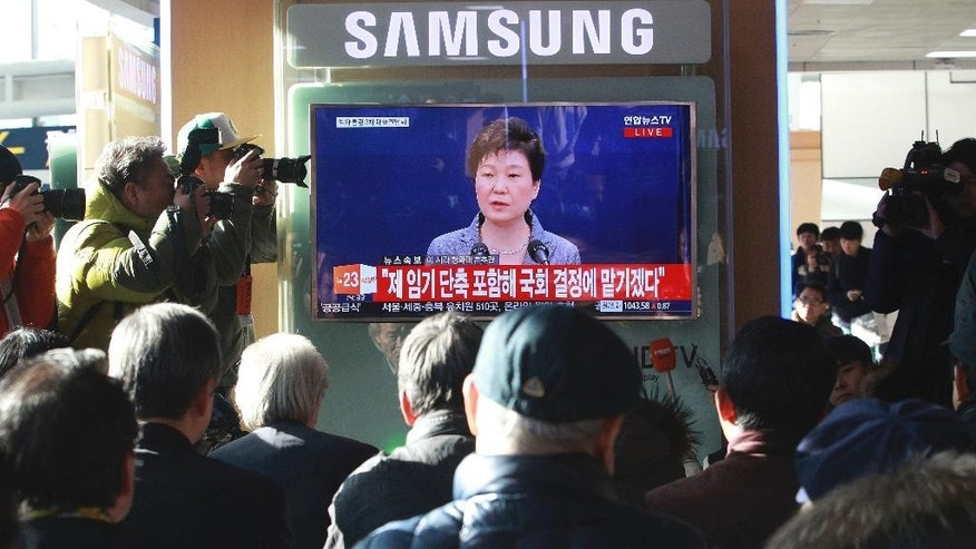 People watch a TV screen showing the live broadcast of South Korean President Park Geun-hye's addressing to the nation, at the Seoul Railway Station in Seoul, South Korea, Tuesday, Nov. 29, 2016. The embattled South Korean president says she'll resign if parliament comes up with a plan for the safe transfer of power. (AP Photo/Ahn Young-joon)
