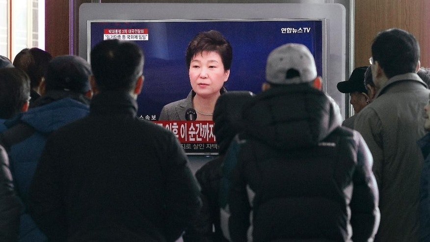 People watch a live broadcast of South Korean President Park Geun-hye addressing the nation at the Seoul Railway Station in Seoul, South Korea, Tuesday, Nov. 29, 2016. The embattled president says she'll resign if parliament comes up with a plan for the safe transfer of power. President Park Geun-hye's stunning announcement Tuesday comes after massive protests that have called for her ouster amid a mounting scandal. (AP Photo/Ahn Young-joon)