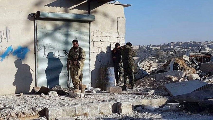 This Sunday, Nov. 27, 2016 photo provided by the Rumaf, a Syrian Kurdish activist group, which has been authenticated based on its contents and other AP reporting, shows Kurdish fighters watch people flee from rebel-held eastern neighborhoods of Aleppo into the Sheikh Maqsoud area that is controlled by Kurdish fighters, Syria. Syrian state media is reporting that government forces have captured the eastern Aleppo neighborhood of Sakhour, putting much of the northern part of Aleppo's besieged rebel-held areas under state control. (The Rumaf via AP)