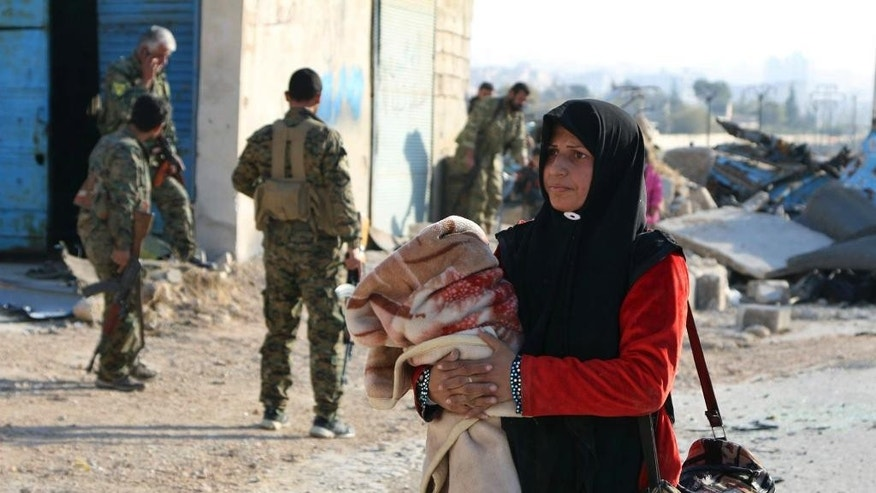 This Sunday, Nov. 27, 2016 photo provided by the Rumaf, a Syrian Kurdish activist group, which has been authenticated based on its contents and other AP reporting, shows a Syrian woman carrying her belongings pass by Kurdish fighters, as she flees rebel-held eastern neighborhoods of Aleppo into the Sheikh Maqsoud area that is controlled by Kurdish fighters, Syria. Syrian state media is reporting that government forces have captured the eastern Aleppo neighborhood of Sakhour, putting much of the northern part of Aleppo's besieged rebel-held areas under state control. (The Rumaf via AP)