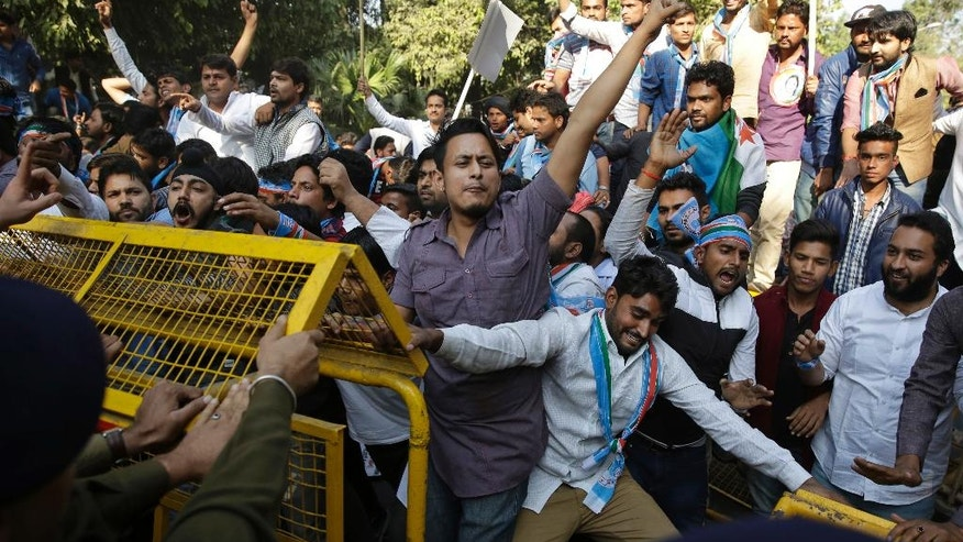 Members of the National Students Union of India (NSUI), student wing of India's main opposition Congress party, try to cross barricades during a protest against the government's decision to withdraw high denomination notes from circulation, in New Delhi, India, Monday, Nov. 28, 2016. Indian Prime Minister Narendra Modi, in his Nov. 8 televised address, announced the demonetization of India's 500 and 1,000-rupee notes, which made up 86 percent of the country's currency. He said it would wipe out rampant corruption, though in a country of 1.3 billion where most people don't have bank accounts, it also wiped out legally collected savings. (AP Photo/Tsering Topgyal)