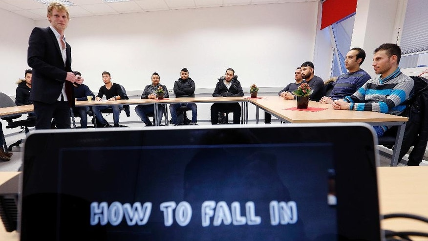 "In this Nov. 22, 2016 photo refugees take part in a flirt workshop called 'how to fall in love in Germany"" in Dortmund, Germany. Teacher Horst Wenzel, left, who usually teaches German men how to approach women, volunteers his skills to help with integrating some of the more than 1 million refugees who have arrived over the past two years in Germany. (AP Photo/Michael Probst)"
