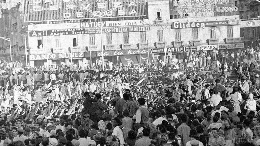 FILE - This Jan. 7, 1959 file photo shows a crowd surrounding Fidel Castro, center right, waving from a small personnel carrier in Santa Clara, Cuba, as he and his troops make their way to Havana where a provisional government had assumed power. After his band of bearded rebels won power in 1959, Castro embarked on a victory tour delivering speeches to cheering crowds stretching from the eastern Cuban city of Santiago to Havana. Starting Nov. 30, 2016, his ashes will retrace that journey in a solemn procession to his final resting spot. (AP Photo, File)
