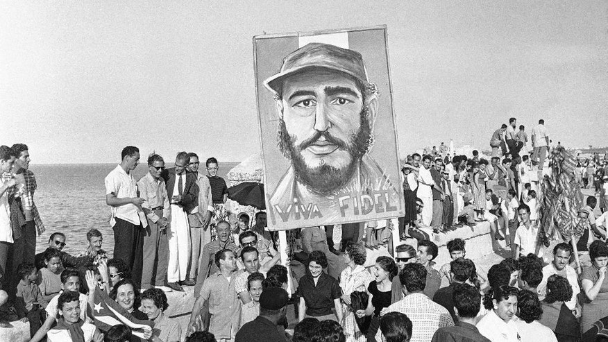 """FILE -  In this Jan. 8, 1959 file photo, supporters of rebel leader Fidel Castro carry a painting of their hero during a welcome rally along the Malecon in Havana, Cuba, after Castro toppled dictator Fulgencio Batista and makes his way from Santiago in a victory tour. As Castro's remains are prepared for the return to Santiago, the state is rekindling images of a younger Castro whose legacy they vow to keep alive. The signs says in Spanish """"Long live Fidel!"""" Castro died on Nov. 25, 2016 at age 90.  (AP Photo, File)"""