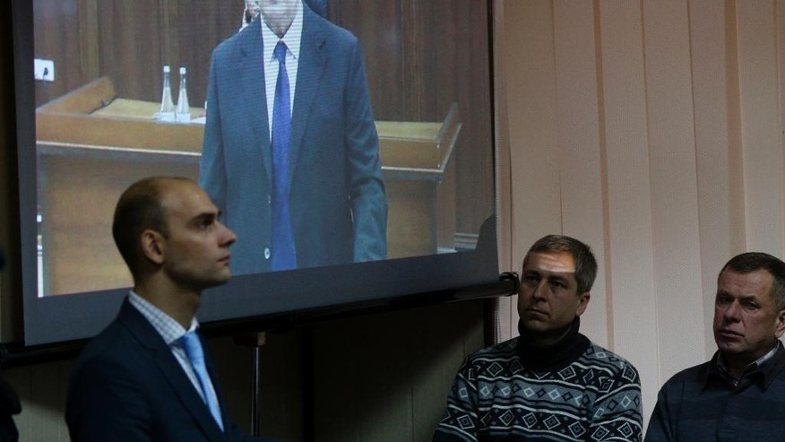 """Officials listen to former Ukrainian president Viktor Yanukovych at a court room in Kiev, Ukraine, Monday, Nov. 28, 2016. Yanukovych, who gave testimony to a Kiev court on Monday from a courtroom in Russia, said he did not give orders to his forces to open fire on protesters and """"could not have possibly given such orders."""" (AP Photo/Sergei Chuzavkov)"""