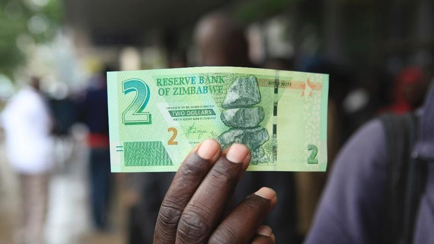A man shows a new note introduced by the Reserve Bank of Zimbabwe in Harare, Monday, Nov, 28, 2016. Zimbabwe has rolled out a new currency for the first time since 2009 in hopes of easing biting shortages of the US dollar. Banks across the country started issuing the new currency called bond notes, Monday(AP Photo/Tsvangirayi Mukwazhi)