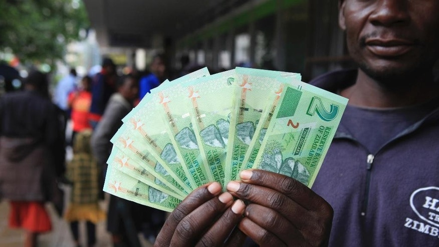 A man shows the new notes introduced by the Reserve Bank of Zimbabwe in Harare, Monday, Nov, 28, 2016. Zimbabwe has rolled out a new currency for the first time since 2009 in hopes of easing biting shortages of the US dollar. Banks across the country started issuing the new currency called bond notes, Monday. (AP Photo/Tsvangirayi Mukwazhi)