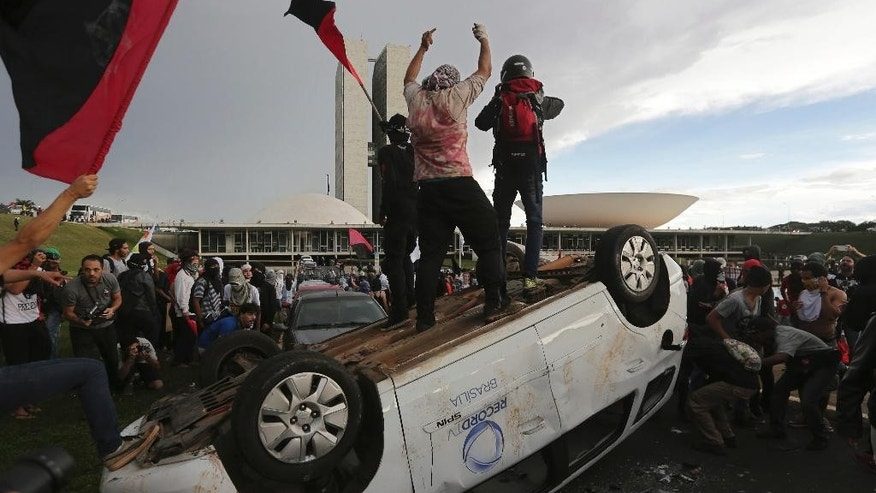 Protesters stand on an overturned car outside Congress where senators planned to vote on a spending cap bill and the lower Chamber of Deputies was considering controversial anti-corruption legislation, in Brasilia, Brazil, Tuesday, Nov. 29, 2016. Brazil, home to Latin America's largest economy, is suffering its worst recession in decades. (AP Photo/Eraldo Peres)