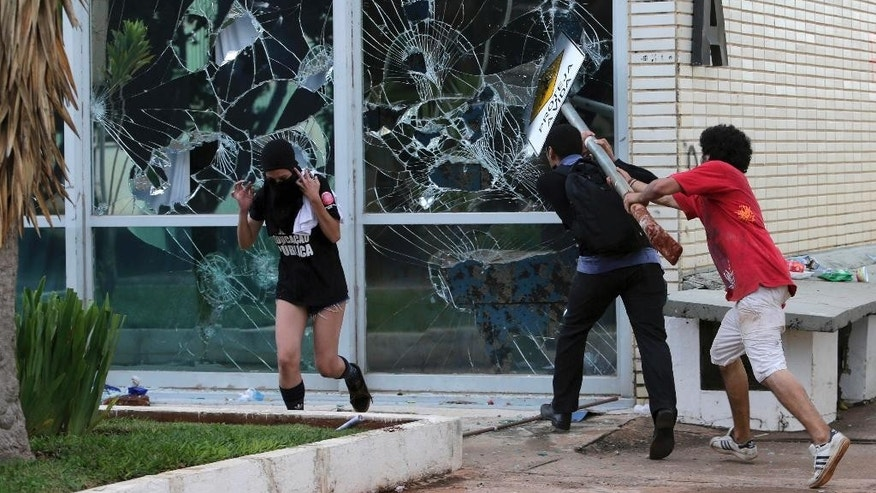 Protesters break windows at the Agrarian Development Ministry near Congress where senators planned to vote on a spending cap bill and the lower Chamber of Deputies was considering controversial anti-corruption legislation, in Brasilia, Brazil, Tuesday, Nov. 29, 2016. Brazil, home to Latin America's largest economy, is suffering its worst recession in decades. (AP Photo/Eraldo Peres)
