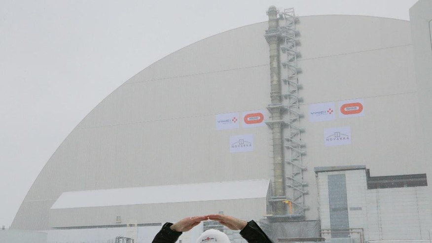 A worker explains a structure of an arch-shaped enclosure in Chernobyl, Ukraine, Tuesday, Nov. 29, 2016. The gargantuan arch-shaped enclosure has begun slowly moving towards the exploded Chernobyl nuclear reactor, in what represents a significant step toward liquidating the remains of the world's worst nuclear accident. (AP Photo/Efrem Lukatsky)