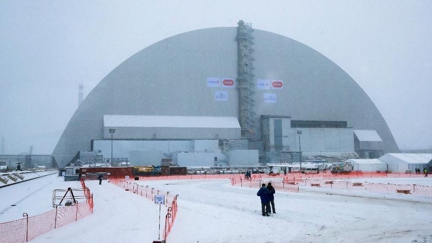 Workers inspect the New Safe Confinement (NSC) movable enclosure at the nuclear power plant in Chernobyl, Ukraine, Tuesday, Nov. 29, 2016. The NSC enclosure has slowly begun to move towards covering the Chernobyl nuclear reactor, in what represents a significant step toward liquidating the remains of the world's worst nuclear accident. (AP Photo/Efrem Lukatsky)