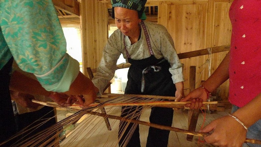 In this Aug. 6, 2016 photo, ethnic minority artisan Pan Mi-shuang weaves fabric using a traditional method in rural Sandu in China's Guizhou province. Pan and other village artisans are working with designer Elaine Ng to put new twists into traditional crafts by Guizhou's ethnic minorities, as Ng hopes to build a sustainable business model that helps preserve skills endangered by China's rapid modernization. (AP Photo/Kelvin Chan)