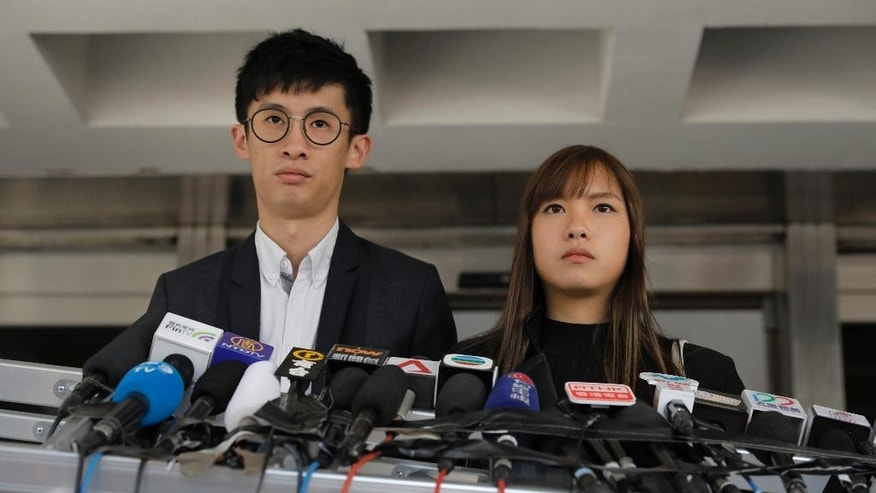 Newly elected Hong Kong lawmakers Sixtus Leung, left, and Yau Wai-ching listen to reporters questions during a press conference outside the high court in Hong Kong, Wednesday, Nov. 30, 2016. The two lawmakers lost their appeal Wednesday against a ruling disqualifying them from office because they altered their oaths with an anti-China insult. (AP Photo/Vincent Yu)