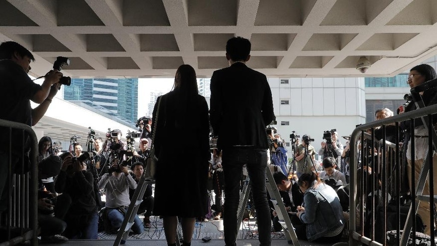 Newly elected Hong Kong lawmakers Sixtus Leung, center right, and Yau Wai-ching, cener left, listen to reporters questions during a press conference outside the high court in Hong Kong, Wednesday, Nov. 30, 2016. The two lawmakers lost their appeal Wednesday against a ruling disqualifying them from office because they altered their oaths with an anti-China insult. (AP Photo/Vincent Yu)