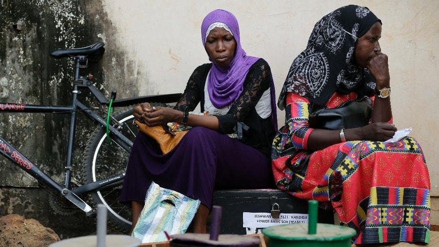 Women sit as they wait outside an independent electoral commission office where election material is being distributed in Banjul, Gambia, Tuesday Nov. 29, 2016. Gambia's opposition parties have come together in an unprecedented coalition hoping to oust the small West African nation's longtime President Yahya Jammeh. (AP Photo/Jerome Delay)