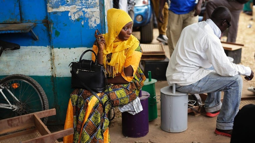 People wait outside an independent electoral commission office where election material is being distributed in Banjul, Gambia, Tuesday Nov. 29, 2016. Gambia's opposition parties have come together in an unprecedented coalition hoping to oust the small West African nation's longtime President Yahya Jammeh. (AP Photo/Jerome Delay)