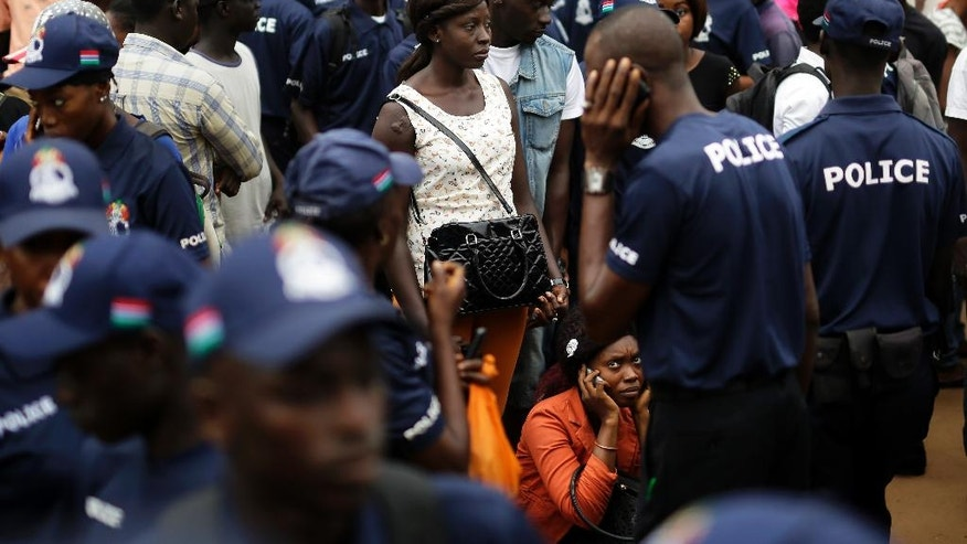 People and police officers gather outside an independent electoral commission office where election materials are being distributed in Banjul, Gambia, Tuesday Nov. 29, 2016. Gambia's opposition parties have come together in an unprecedented coalition hoping to oust the small West African nation's longtime President Yahya Jammeh. (AP Photo/Jerome Delay)