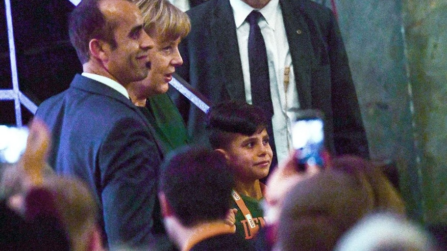 In this Nov. 28, 2016 photo Afghan refugee Edris, right, and his father, left,  meet briefly with German Chancellor Angela Merkel at the civic hall in Heidelberg, southern Germany.  (Uwe Anspach/dpa via AP)