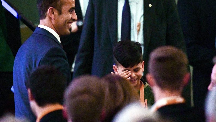 In this Nov. 28, 2016 photo Afghan refugee Edris wipes his eye after he and his father met briefly with German Chancellor Angela Merkel at the civic hall in Heidelberg.  (Uwe Anspach/dpa via AP)