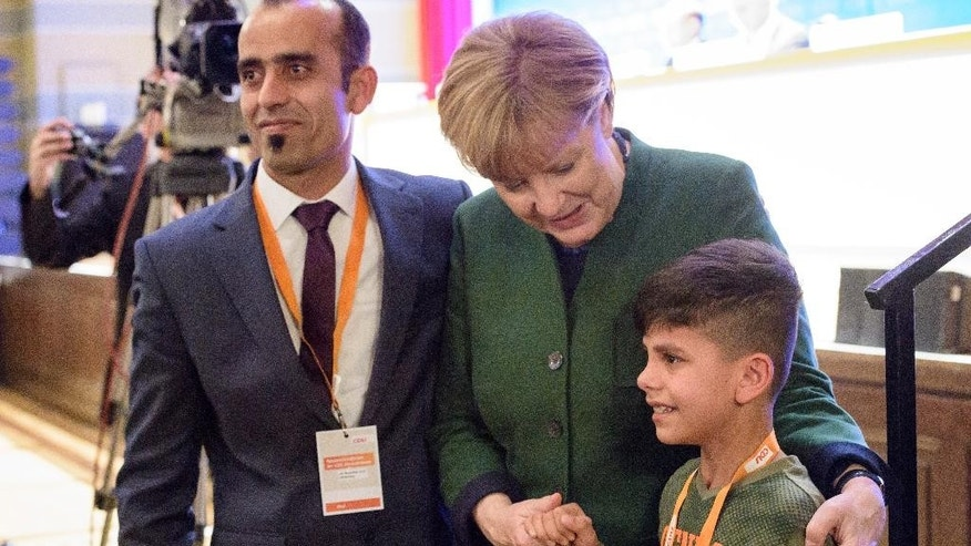 In this Nov. 28, 2016 picture German Chancellor Angela Merkel, center, holds the hand of Afghan refugee boy  Edris, right,during a regional party conference in Heidelberg, Germany. At left the father of the boy. German Chancellor Angela Merkel has moved the  young Afghan boy to tears, shaking his hand after he publicly thanked her at the meeting of Merkel's Christian Democrats. ( Philipp Rothe/dpa via AP)