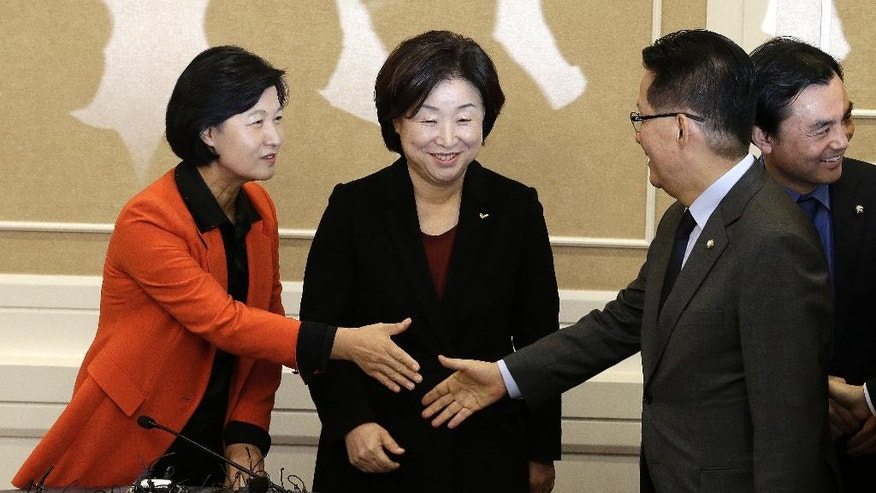 Choo Mi-ae, left, leader of the main opposition Democratic Party, shakes hands with Park Jie-won, interim leader of the People's Party, beside Sim Sang-jung, center, head of the Justice Party, during a meeting at the National Assembly in Seoul, South Korea, Wednesday, Nov. 30, 2016. South Korea's three main opposition parties began talks Wednesday to determine when to try to impeach President Park Geun-hye, dismissing as a stalling tactic her offer to resign if parliament arranges a safe transfer of power. (AP Photo/Ahn Young-joon)