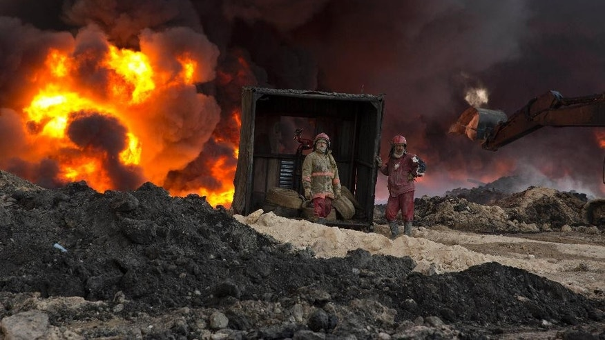 Fire fighters work to quell an oil fire set by Islamic State militants in Qayara, south of Mosul, Iraq, Monday, Nov. 28, 2016. (AP Photo/Maya Alleruzzo)
