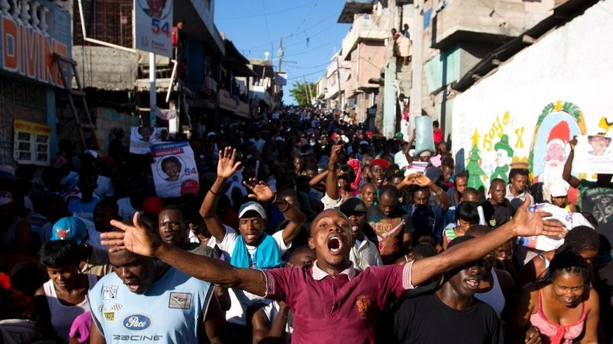 Supporters of presidential candidate Maryse Narcisse, from Fanmi Lavalas political party, chant victory slogans during a protest in Port-au-Prince, Haiti, Monday, Nov. 28, 2016.  Before election results have been announced, supporters of Narcisse assert their candidate has won, and that only electoral fraud would keep her from office. (AP Photo/Dieu Nalio Chery)