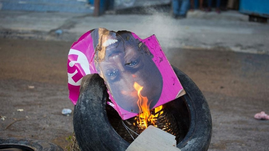 A campaign poster of presidential candidate Jovenel Moise, from PHTK party, burns after it was set on fire by supporters of rival candidate Maryse Narcisse, from Fanmi Lavalas political party, during a protest in Port-au-Prince, Haiti, Monday, Nov. 28, 2016. Before results have been announced, supporters of Narcisse assert their candidate has won, and that only electoral fraud would keep her from office. (AP Photo/Dieu Nalio Chery)