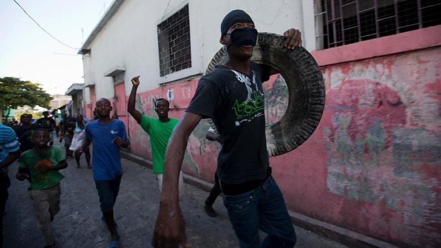 A supporter of presidential candidate Maryse Narcisse, from Fanmi Lavalas political party, carries a tire to burn at a roadblock during a protest against election results in Port-au-Prince, Haiti, Tuesday Nov. 29, 2016. Jovenel Moise, a political newcomer backed by Haiti's previous elected leader, easily won the presidential election redo, according to preliminary results that were quickly questioned Tuesday by several losing factions. (AP Photo/Dieu Nalio Chery)