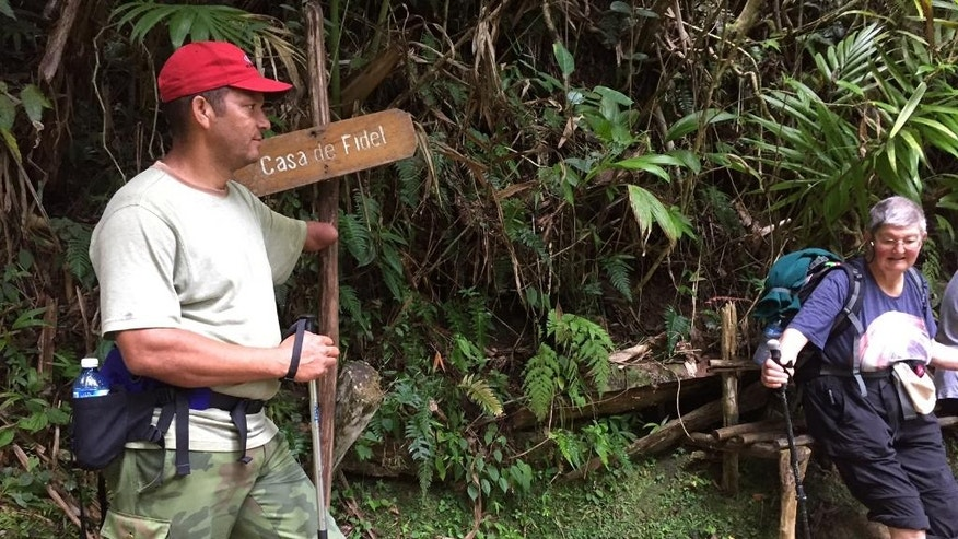 This Nov. 27, 2016 photo shows tour guide Jorge Garcia, outside a shack used by Fidel Castro in the Sierra Maestra mountains near La Plata, Cuba. Castro launched his guerrilla war 60 years ago from a jungle command center in this area. Hikers on a tour of Castro's footsteps heard the news of his death via a crackling two-way radio, their sole link to the outside world. (AP Photo/Karin Laub)