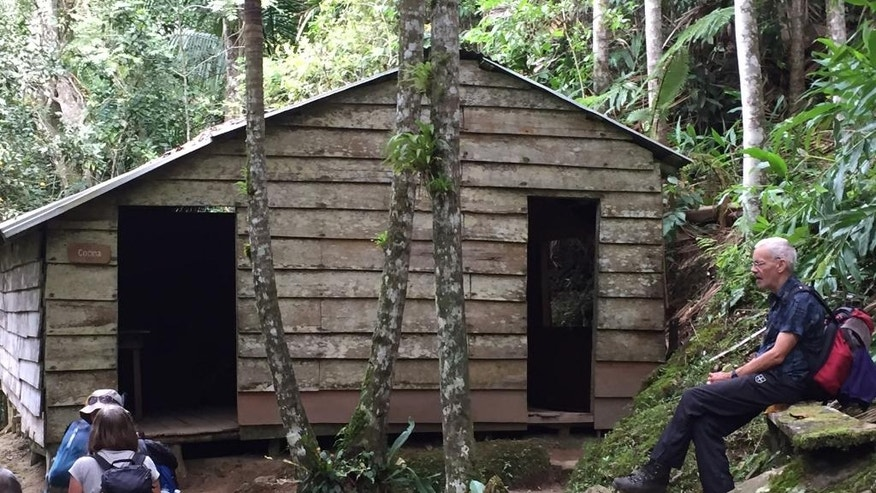 This Nov. 27, 2016 photo shows hikers outside of the kitchen in the compound near La Plata, Cuba, that served as a jungle command center for Fidel Castro when he launched his guerrilla war 60 years ago from the Sierra Maestra mountains. Hikers on a tour of Castro's footsteps heard the news of his death via a crackling two-way radio, their sole link to the outside world. (AP Photo/Karin Laub)