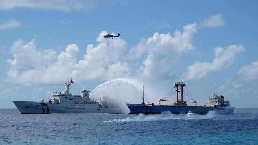 A Taiwan Coast Guard ship, left, and cargo ship take part in a search-and-rescue exercise off of Taiping island in the South China Sea, Tuesday, Nov. 29, 2016, as part of Taiwan's efforts to cement its claim to a key island in the strategically vital waterbody. Eight vessels and three aircraft took part in Tuesday's drill, which simulated a fire aboard a cargo ship that forced crew members to seek safety on Taiping in the Spratly island group. (AP Photo/Johnson Lai)