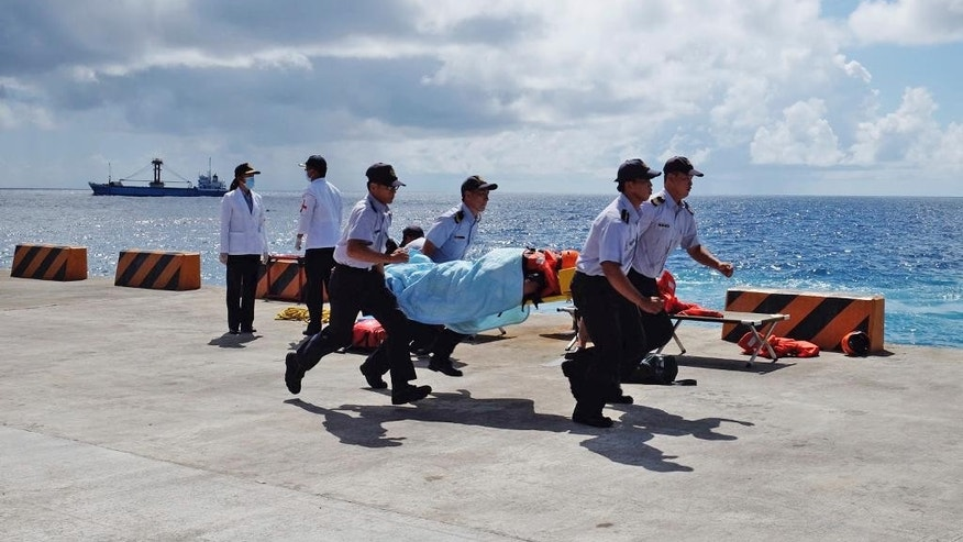 Taiwanese Coast Guard carry a mock victim during a search-and-rescue exercise on Taiping island in the South China Sea, Tuesday, Nov. 29, 2016, as part of Taiwan's efforts to cement its claim to a key island in the strategically vital waterbody. Eight vessels and three aircraft took part in Tuesday's drill, which simulated a fire aboard a cargo ship that forced crew members to seek safety on Taiping in the Spratly island group. (AP Photo/Johnson Lai)