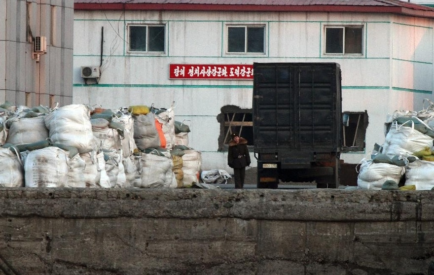 In this March 14, 2016 photo, a North Korean soldier walks past a truck park near the goods pile up on a dockyard in Sinuiju, North Korea, as seen from Dandong in northeastern China's Liaoning province. China on Tuesday, April 5, 2016 imposed restrictions on imports of coal from North Korea and exports of jet fuel to the North in a potentially significant increase in pressure on Pyongyang following U.N. sanctions over its nuclear and missile tests. (Chinatopix via AP) CHINA OUT