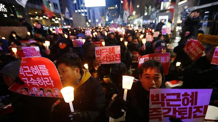 "Protesters shout slogans during a rally calling for South Korean President Park Geun-hye to step down in Seoul, South Korea, Tuesday, Nov. 29, 2016. Park said Tuesday that she'll resign — if parliament arranges the technical details — in her latest attempt to fend off impeachment efforts and massive street protests amid prosecution claims that a corrupt confidante wielded government power from the shadows.The letters read ""Park Geun-hye should step down."" (AP Photo/Ahn Young-joon)"