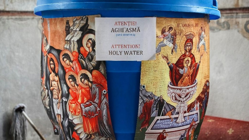 In this Saturday, Oct. 22, 2016 picture a container holding holy water is placed at the entrance of the orthodox patriarchal cathedral in Bucharest, Romania. The feast of St. Dimitrie of Basarobov in Bucharest is an annual demonstration of the strength of Christianity in Romania, and the dominance of the Orthodox branch. (AP Photo/Vadim Ghirda)