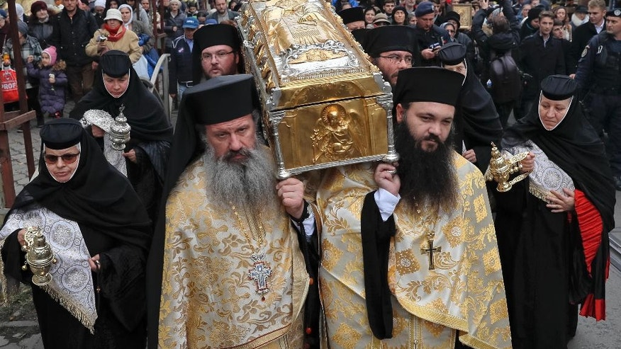 In this Saturday, Oct. 22, 2016 picture priests carry the remains of Saint Dimitrie Bassarabov, during a pilgrimage, in Bucharest, Romania. The Romanian Orthodox and Catholic churches staged pilgrimages parading holy remains. The Catholics have a few drops of the blood of Saint John Paul II; the Orthodox claim to have the remains of three saints including those of St. Dimitrie, the patron saint of Bucharest. (AP Photo/Vadim Ghirda)